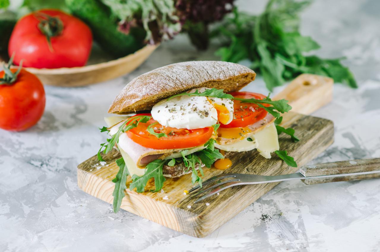 Delicious ciabatta sandwich with ham, tomatoes, arugula and egg poached. Homemade healthy italian sandwich.