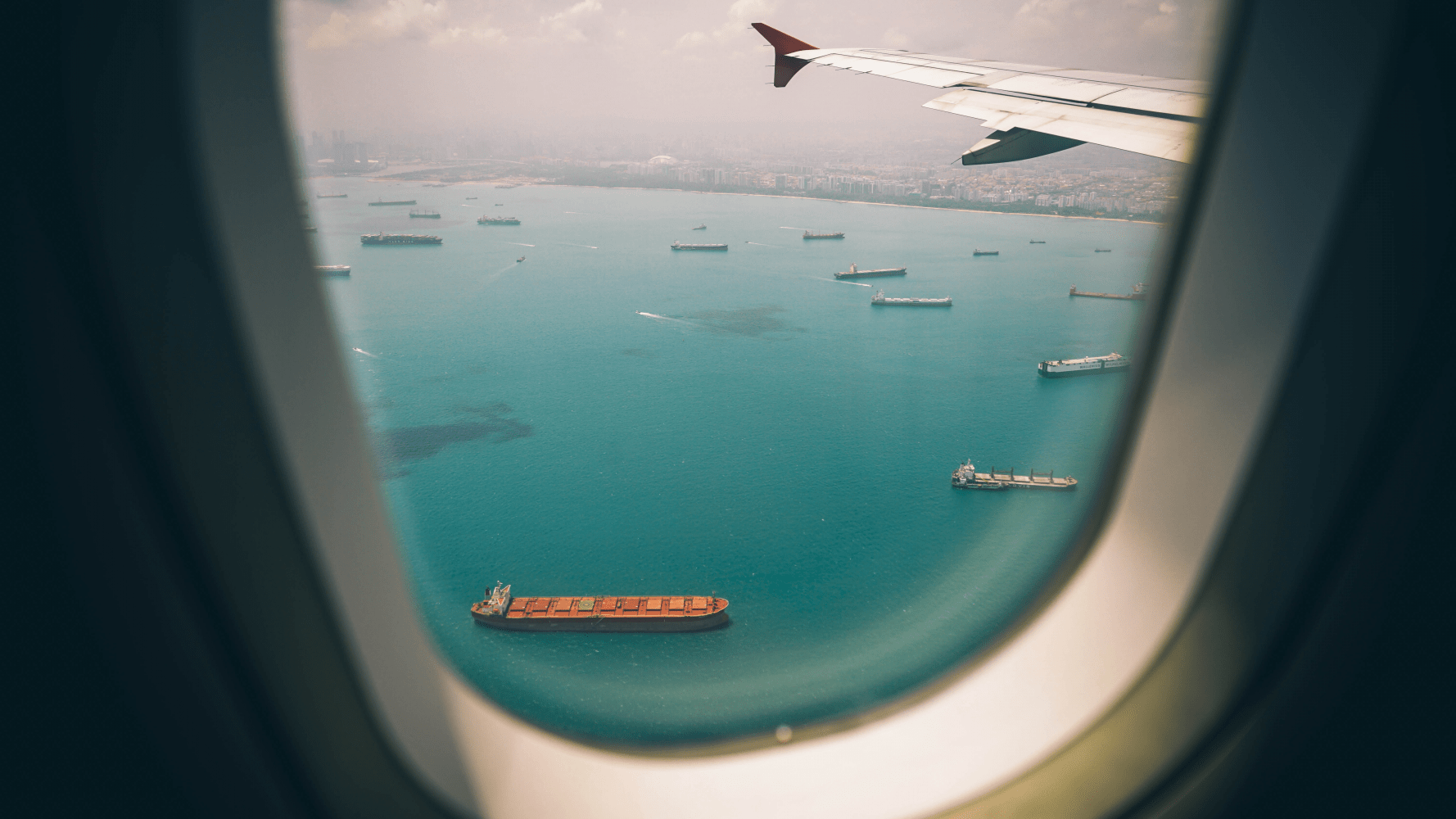 View from the passenger window of a commercial jet overlooking a busy harbor and large container ships