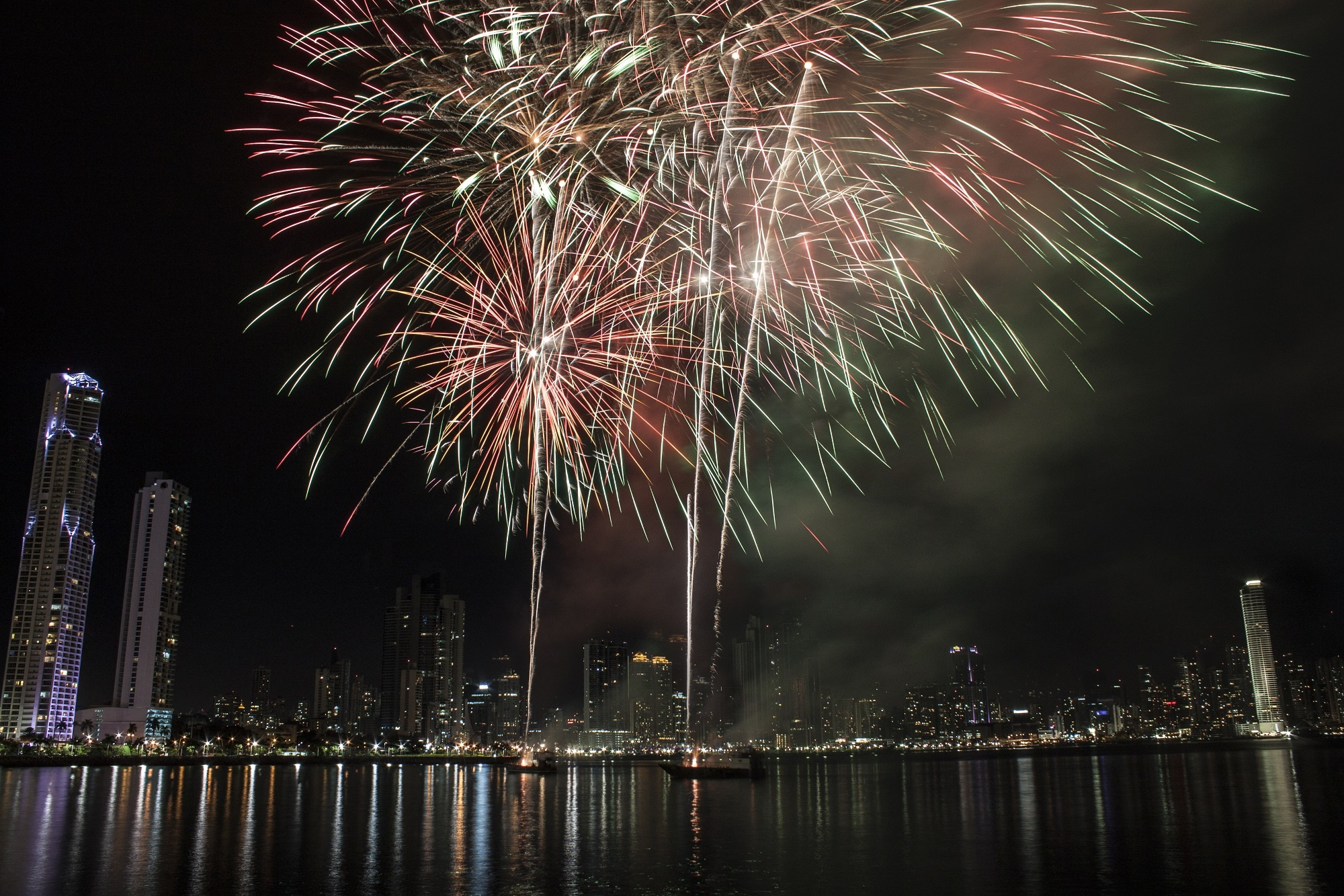 Fireworks exploding over a modern city's harbor at night