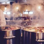 Chef working in an industrial kitchen with two large pots on the stove