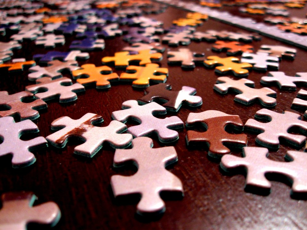 Several pieces of a large puzzle strewn out over a wooden table