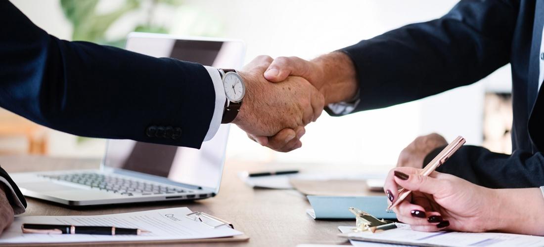 Business handshake across a desk