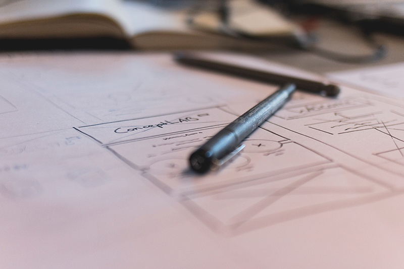 Design mockups drawn in pen on a piece of white paper