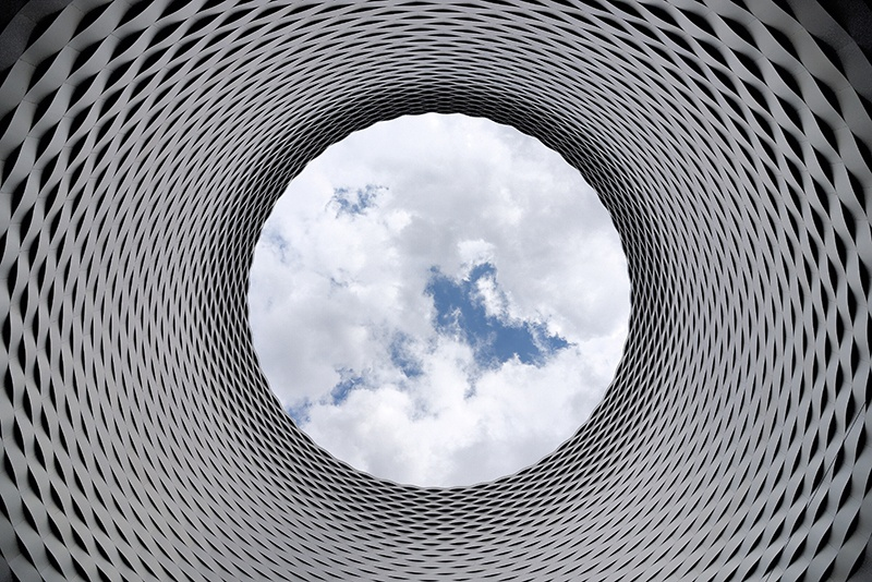 Ground-level view looking up at the clouds through a large abstract modern piece of sculpture or architecture