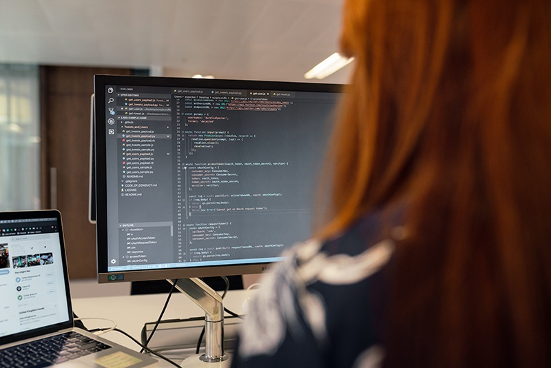 Engineer sitting at a computer desk writing code