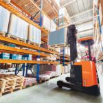 Forklift operator using a forklift to load a pallet of goods onto a warehouse shelf