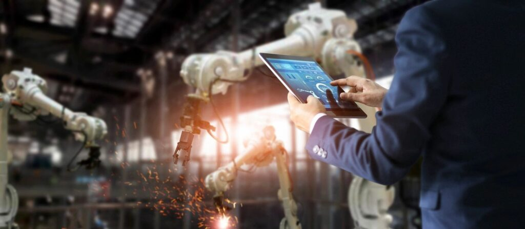 Business executive uses a dashboard on their tablet as robotic arms work in a factory in the background