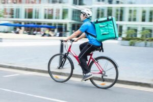 Restaurant delivery-person riding a bicycle on a city street