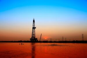 Large oil equipment close to water at sunset