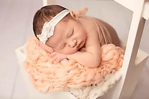 Baby sleeping on peach colored blanket