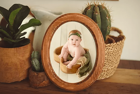 baby photo in oval wood frame