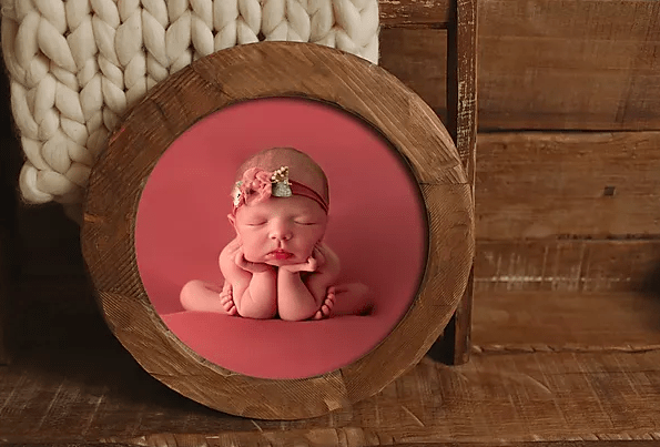 newborn photo in round wood frame