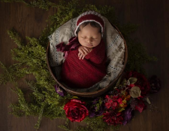newborn in basket with red blanket