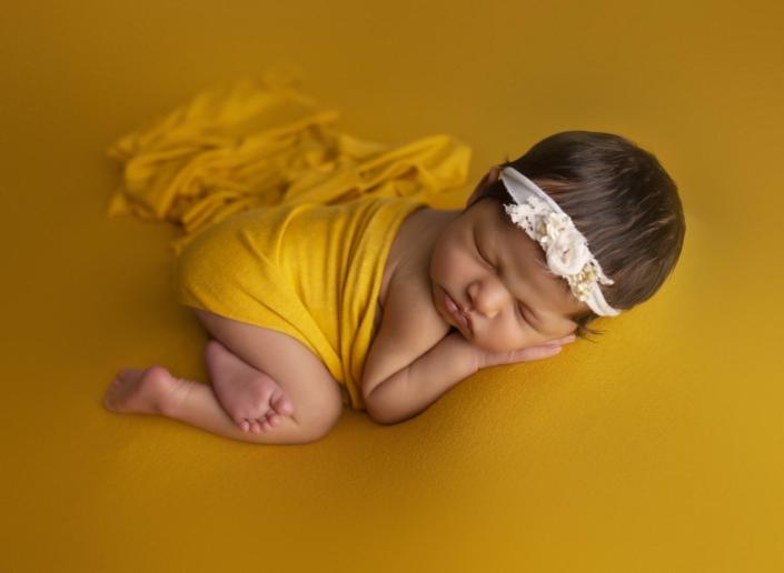 Baby sleeping with yellow background