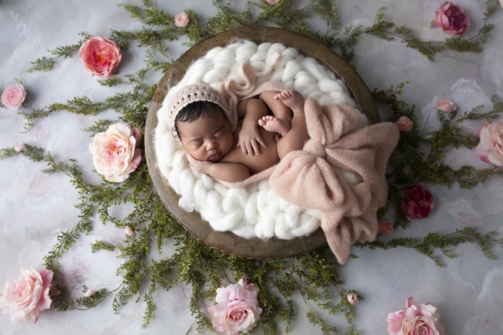 Baby in basket surrounded by flowers