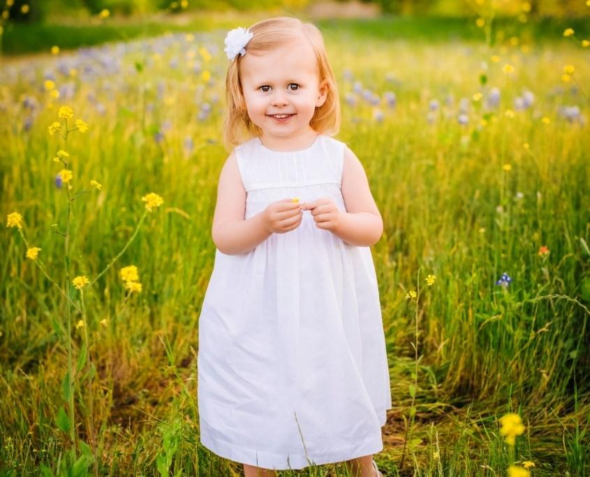 Little girl standing on summer field