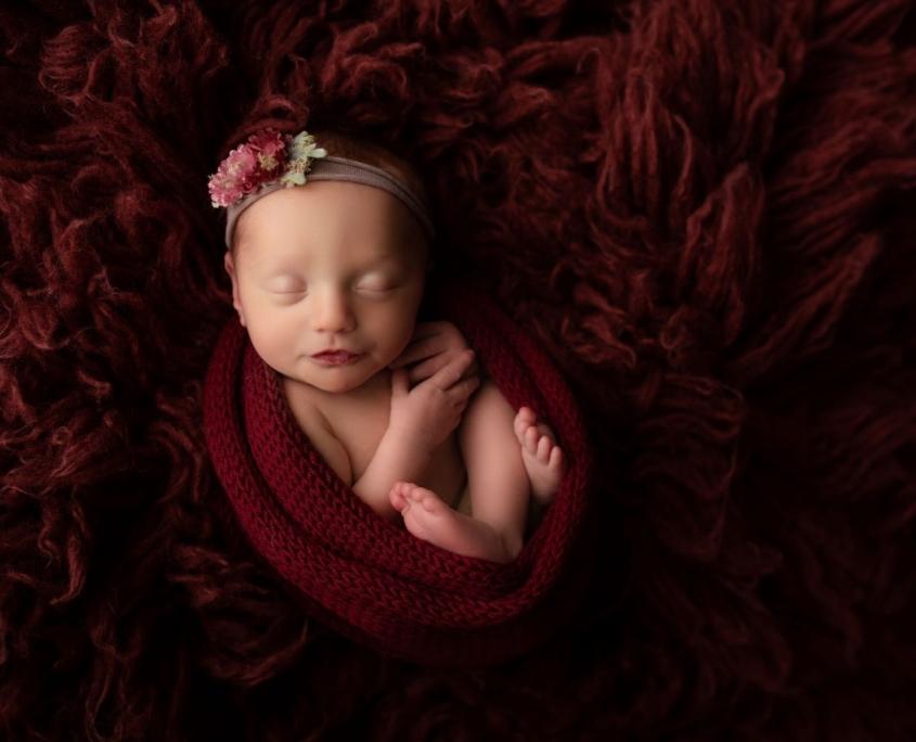 Newborn in red blanket