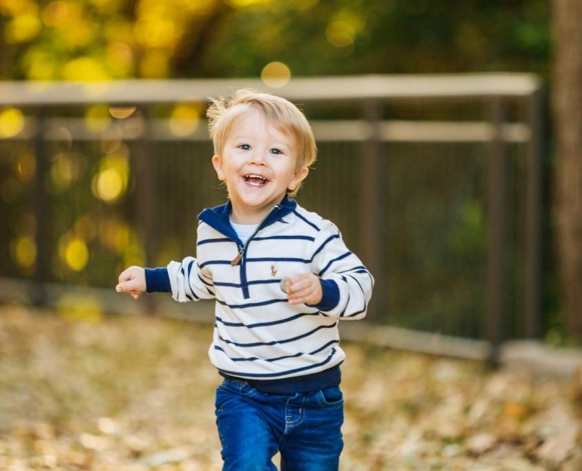 Little boy running among autumn leaves