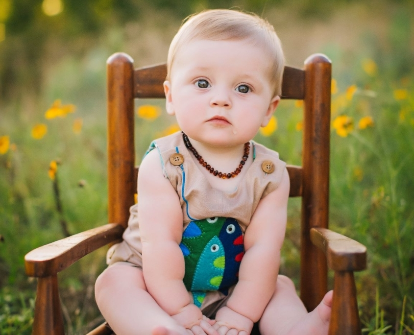 Infant sitting on wooden chair in summer field