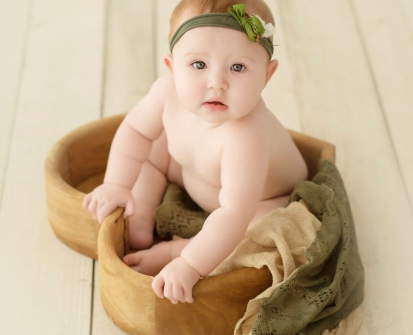 Baby sitting in heart shaped tray