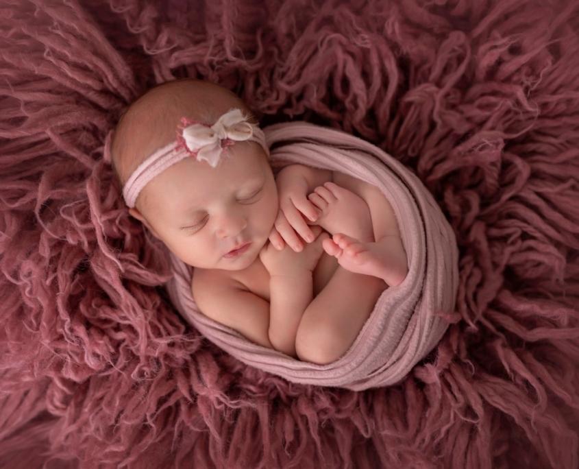 Newborn session with pink flokati rug