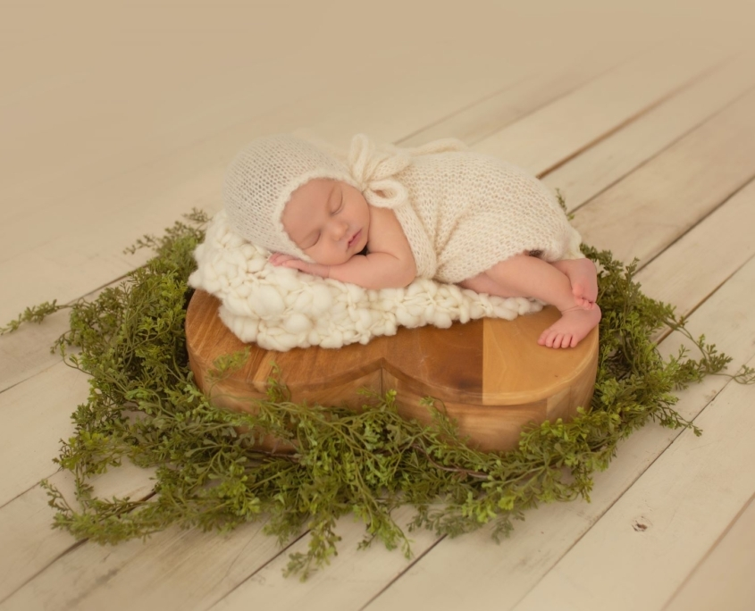 Sleeping newborn on heart shaped wooden piece