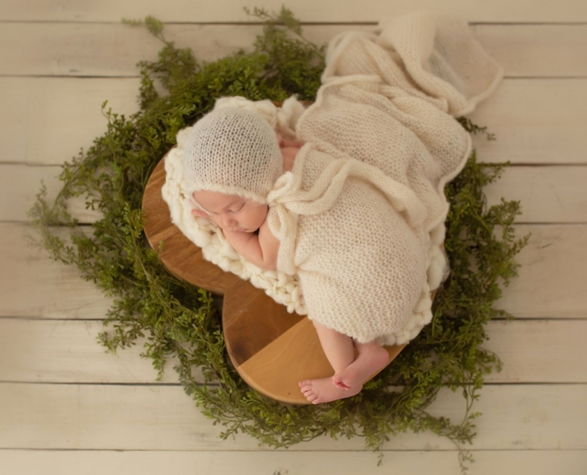 Newborn portrait on heart shaped wooden piece