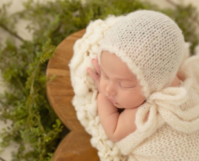 Newborn portrait with white bonnet