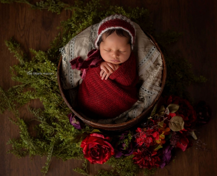 Newborn with red blanket