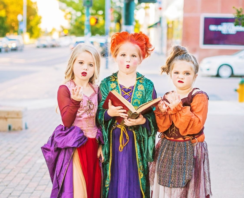 Three girls wearing witch costumes