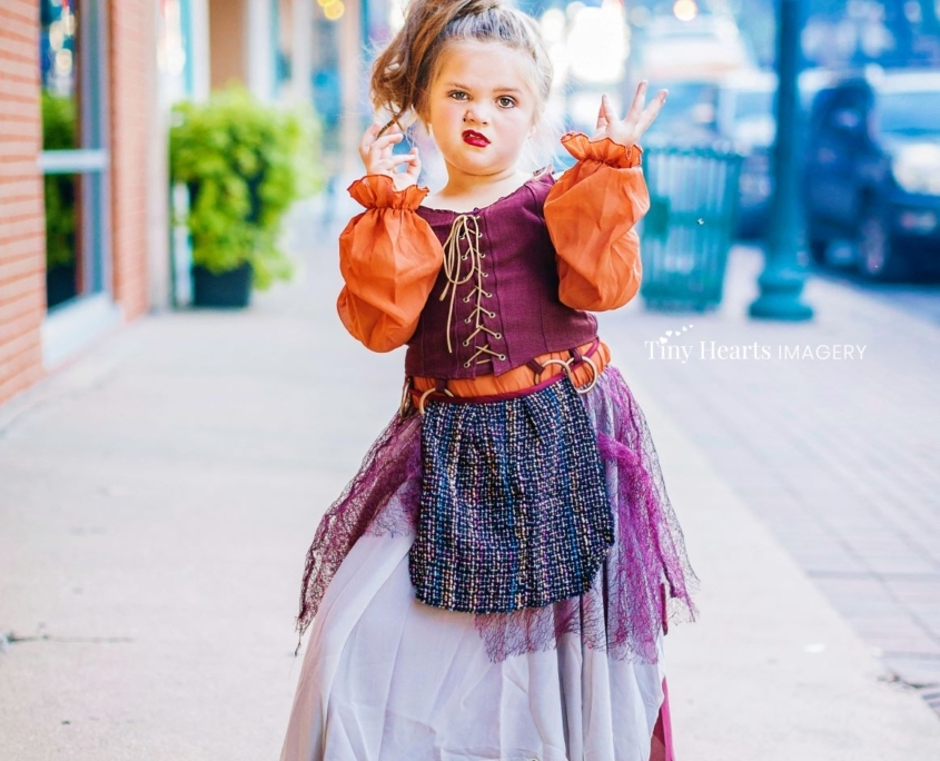 Girl dressed as witch posing on sidewalk