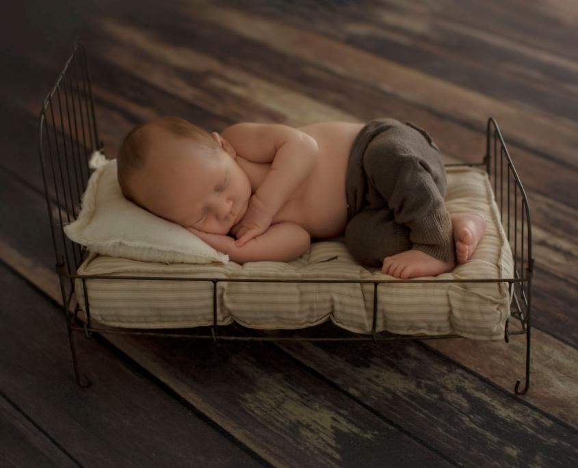 Newborn sleeping on tiny metal bed