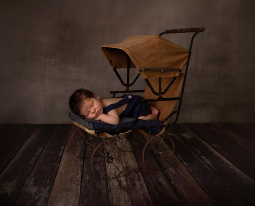 Baby boy in vintage stroller