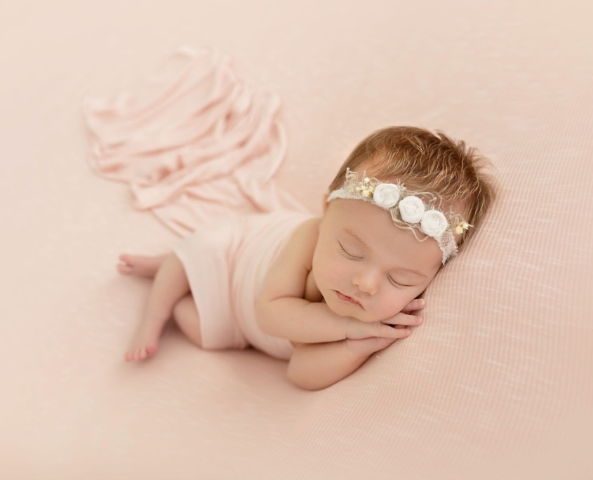 Newborn girl with pink backdrop