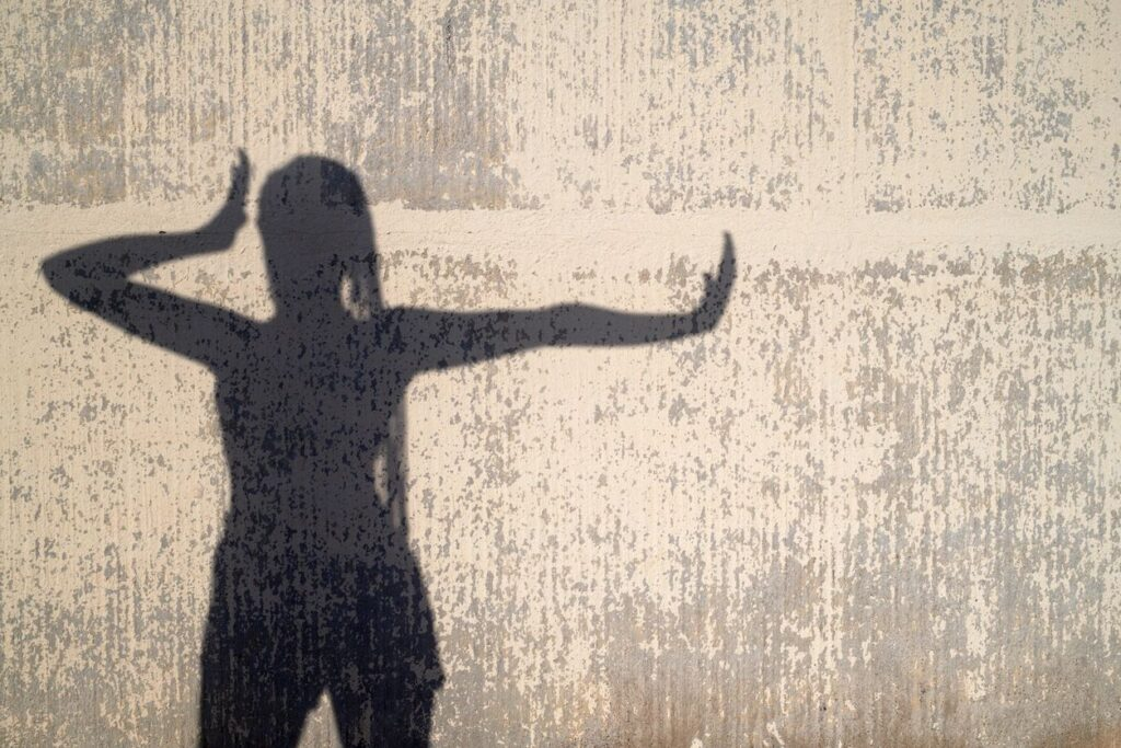 shadow of a person saying stop