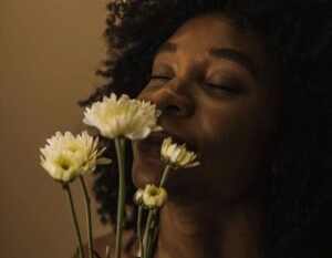 woman smelling daisies