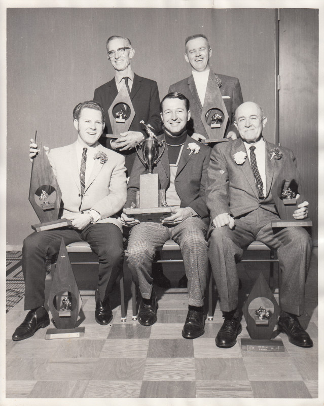 Five people with trophies