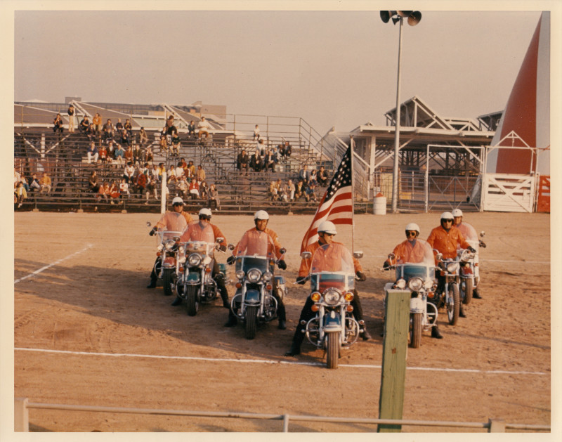 Group of people riding motorcycles in a V formation