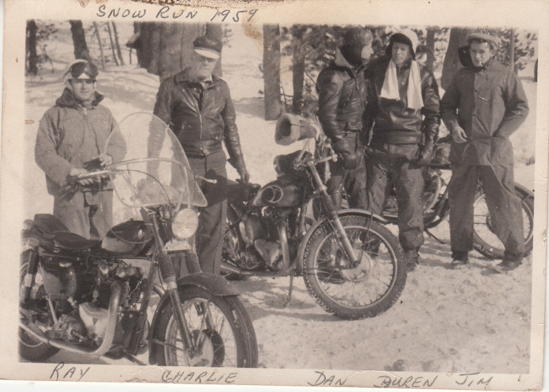 people standing around motorcycles