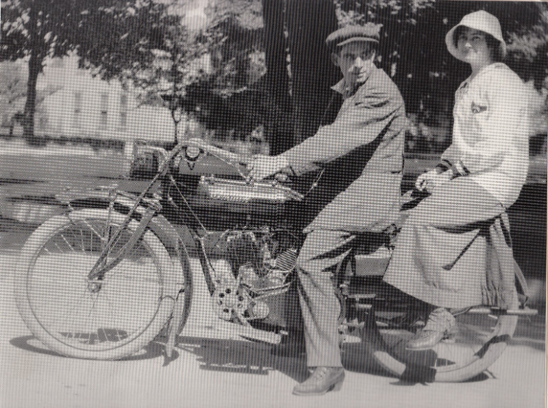 Two people riding on a motorcycle with a dirt road