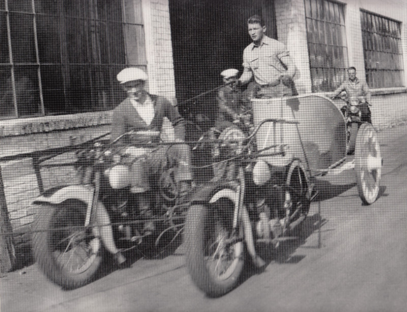 Four people with a motorcycle chariot race