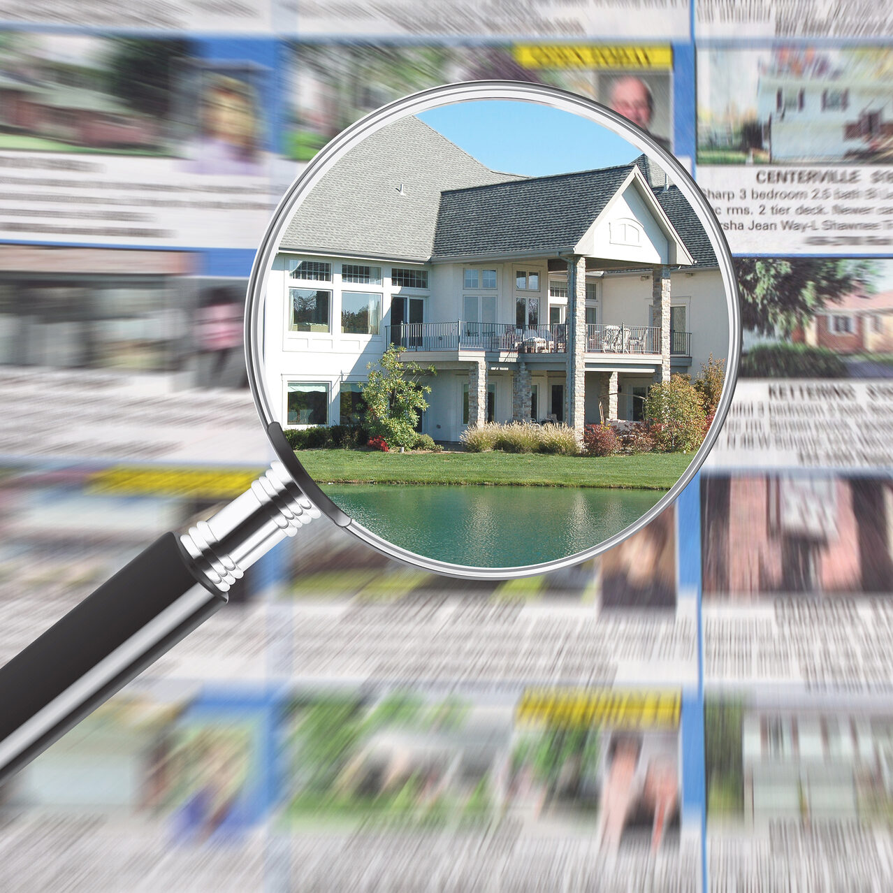 Magnifying glass over real estate section in newspaper