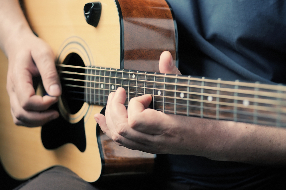 Man playing acoustic guitar in a recording studio