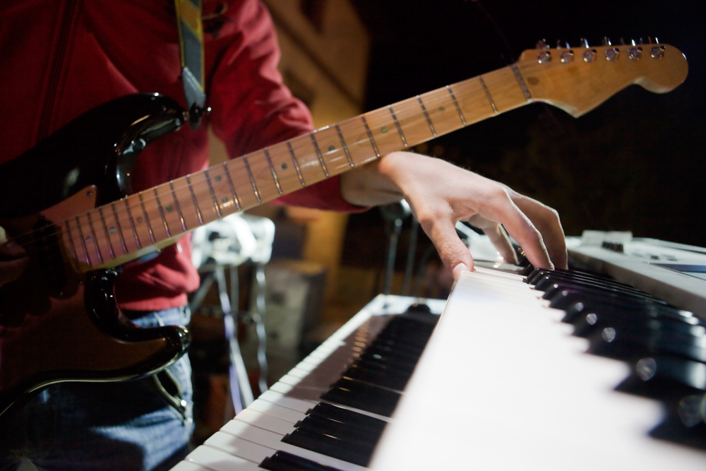 Guitarist playing piano in a recording studio