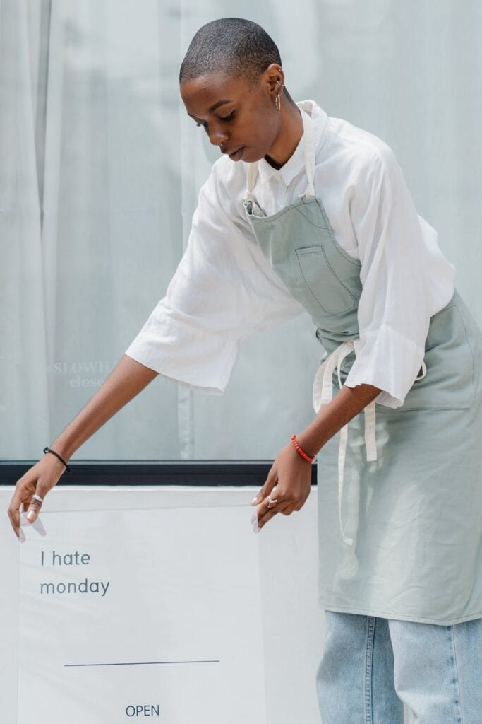 image of a restaurant owner hanging a I hate Monday sign
