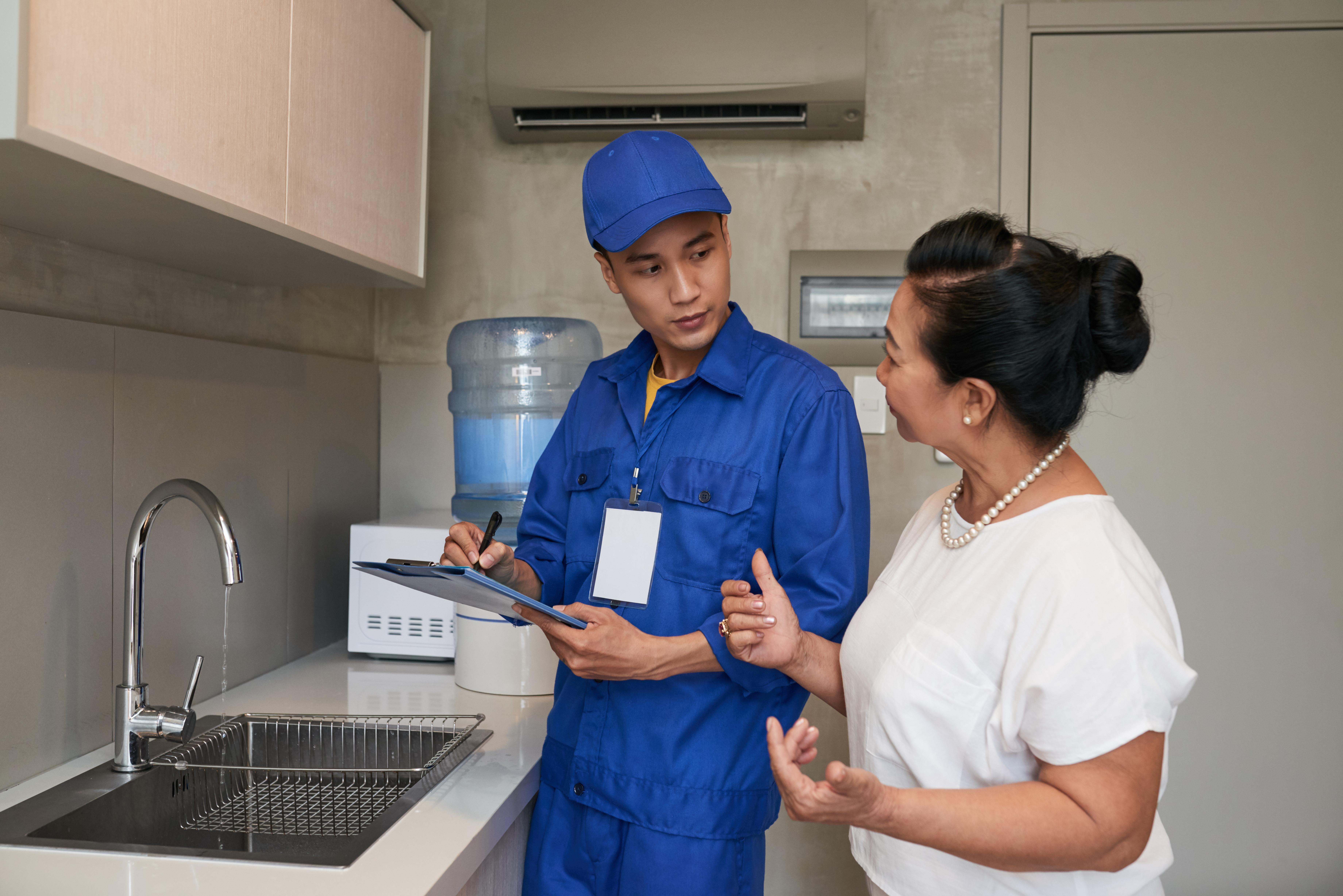 plumber-talking-to-senior-citizen-homeowner