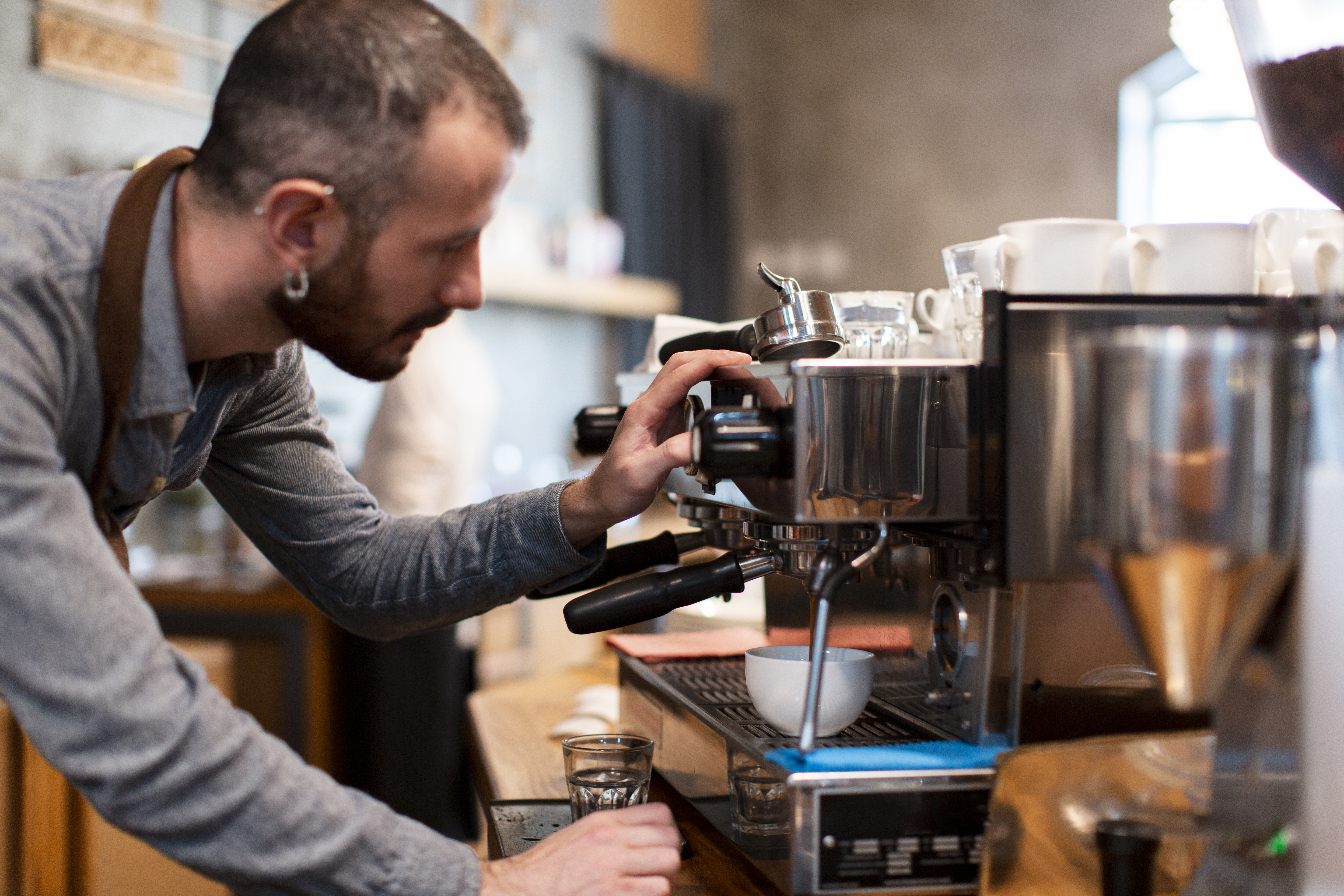 man-drains-coffee-from-cafe-machine