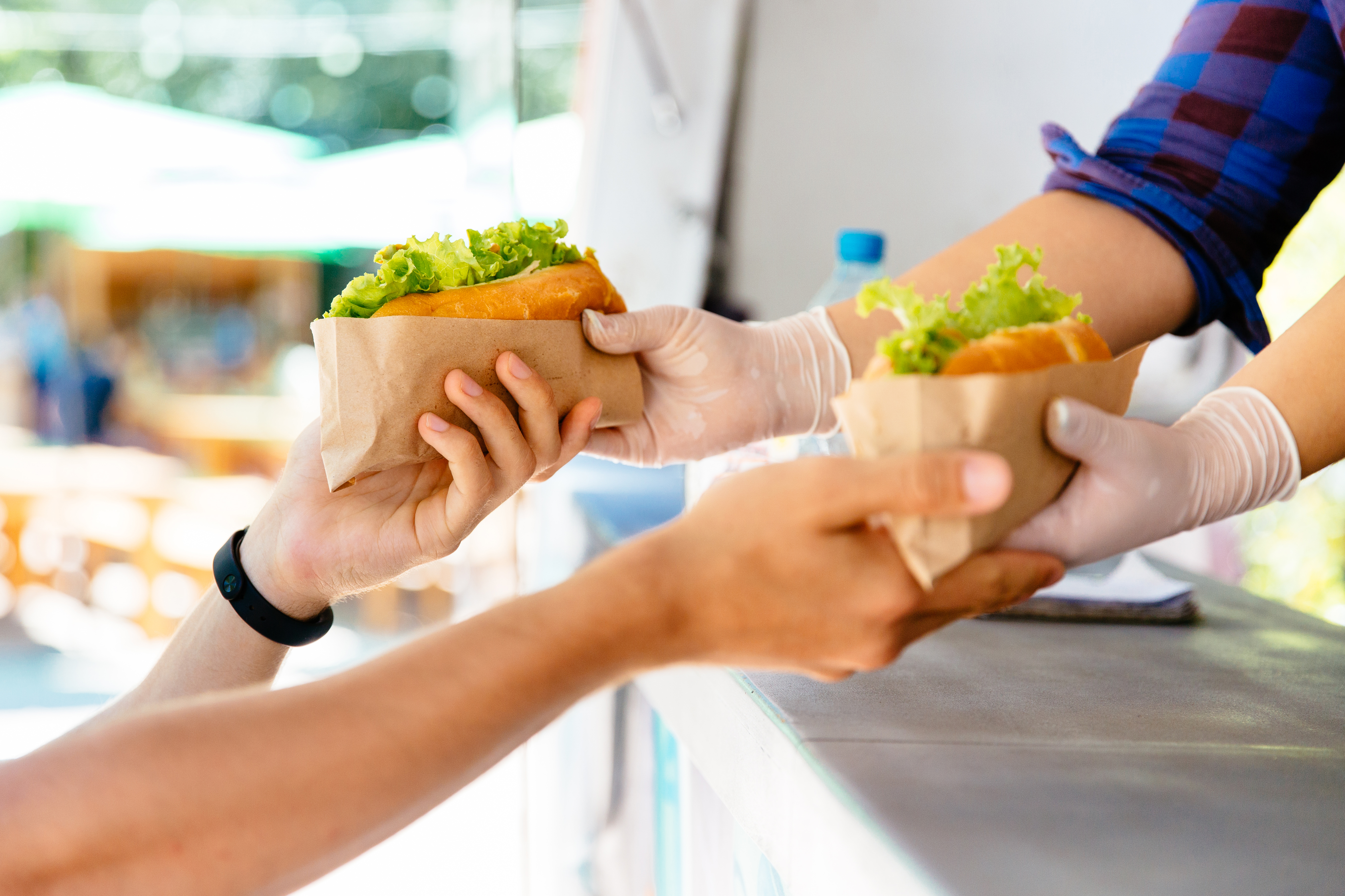 man-buying-two-hot-dogs-at-food-truck-outdoors-street-food-nodat-app