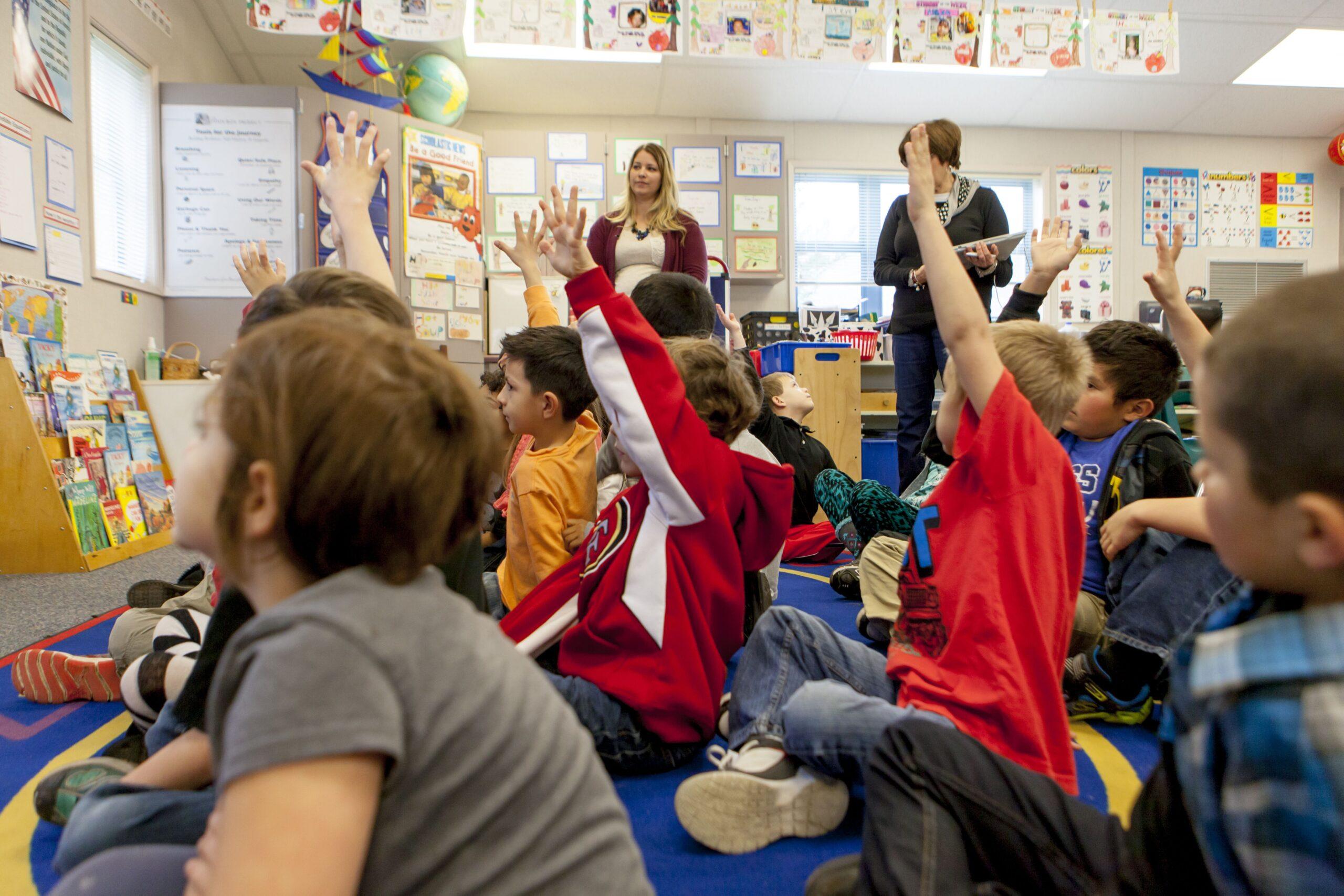students sitting hands raised