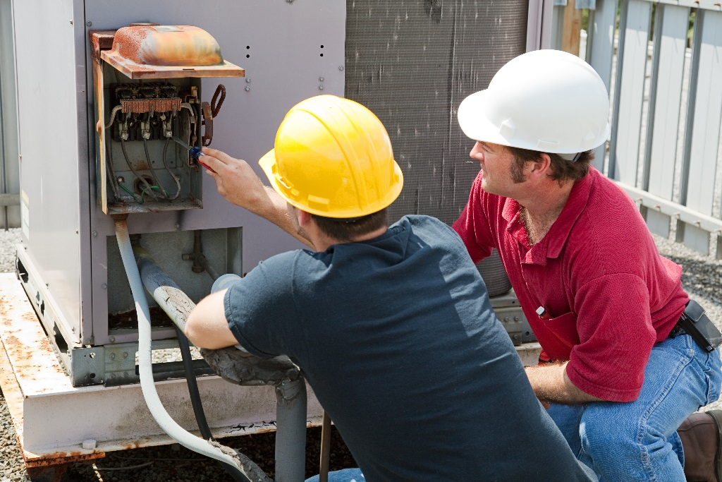 Two AC technicians repairing an industrial air conditioning compressor.